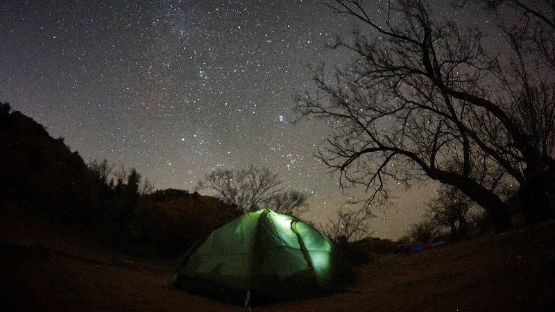 nighttime shot of tent in foreground with the night sky full of stars in background. Shot taken while camping in Palo Duro Canyon