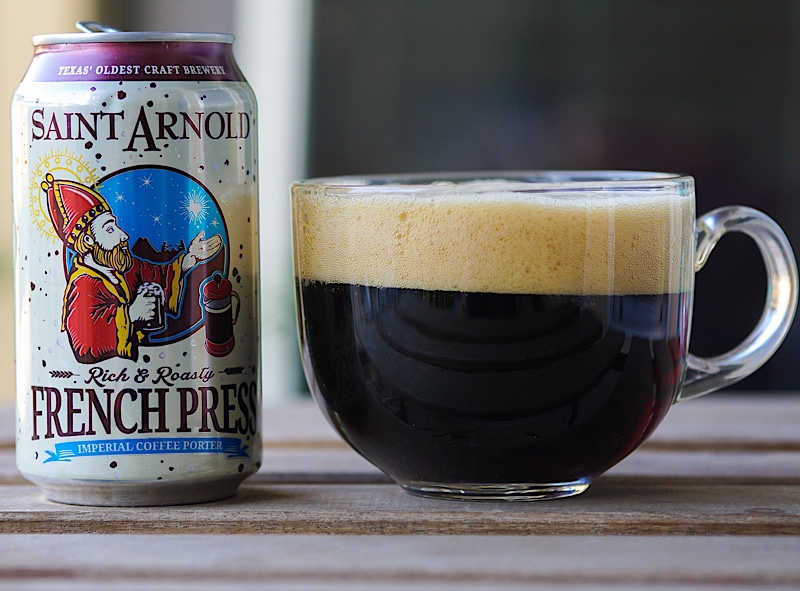 Saint Arnold French Press beer can on table next to clear glass coffee mug full of dark beer