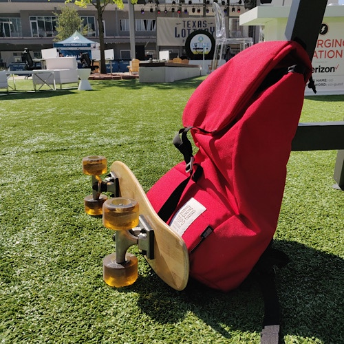 Mini cruiser skateboard sitting next to red backpack on astroturf