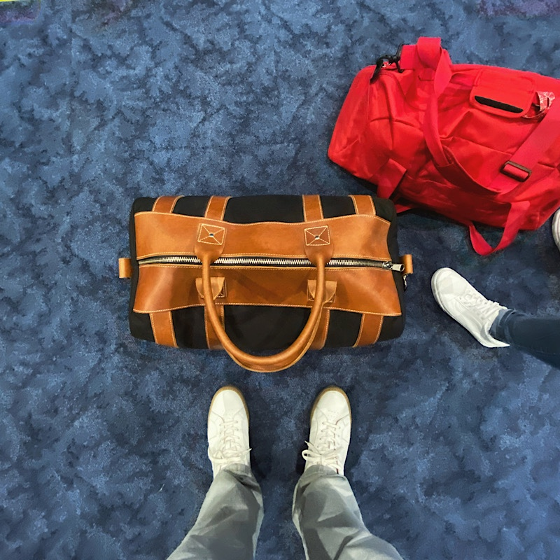 Black duffel bag with light brown leather trim on MIA airport carpet